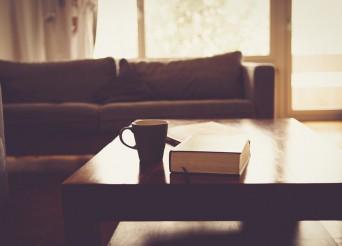 Salon avec canapé au fod une table en bois avec un café et un livre